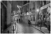 Street with cobblestone pavement and restaurants by night. Quartier Latin, Paris, France ( black and white)