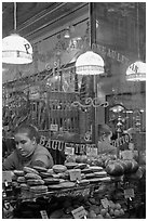 Woman selling pastries and bread in bakery. Paris, France (black and white)