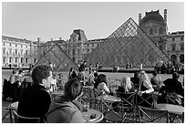 Cafe terrace in the Louvre main courtyard with glass pyramid. Paris, France (black and white)