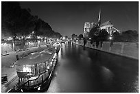 Quay, lighted boats, Seine River and Notre Dame at night. Paris, France (black and white)