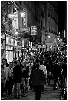 Busy pedestrian street at night. Quartier Latin, Paris, France ( black and white)
