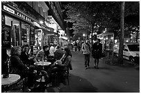 Cafe bar on sidewalk of a Grand Boulevard at night. Paris, France ( black and white)
