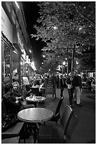 Couple walking by outdoor tables of cafe at night. Paris, France ( black and white)