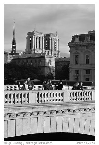 Watching the sunset from a bridge, with Notre Dame towers behind. Paris, France (black and white)