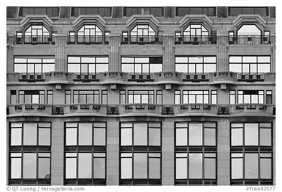 Glass windows of the Samaritaine reflecting colors of sunset. Paris, France (black and white)