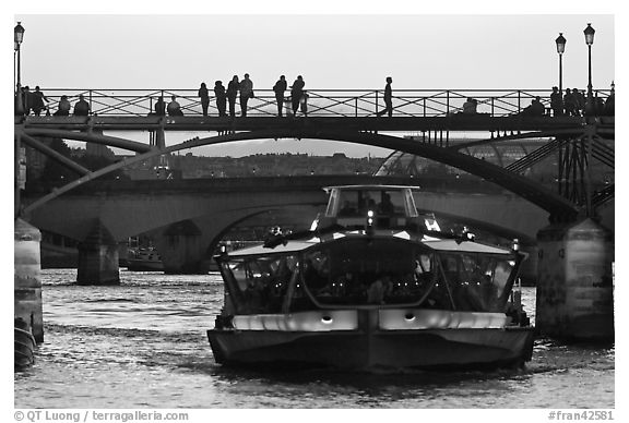 Tour boat below Pont des Arts at sunset. Paris, France (black and white)