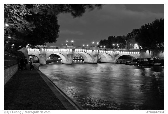Quay, Seine River, and Pont-Neuf at night. Paris, France (black and white)