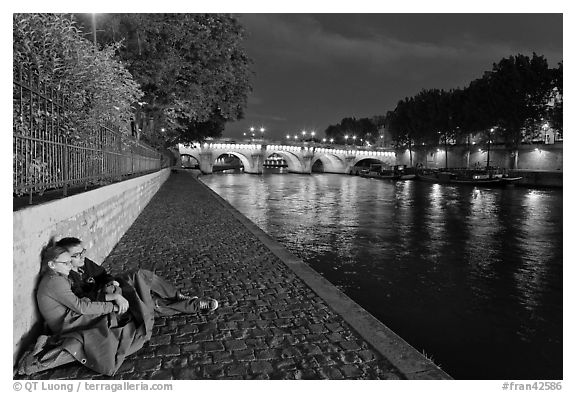 Black and white picture photo couple sitting on quay on banks of the seine river paris france