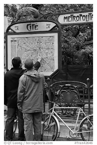 Men looking at a map of the Metro outside Cite station. Paris, France (black and white)