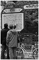 Men looking at a map of the Metro outside Cite station. Paris, France ( black and white)