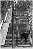 Couple walking up steet stairs, Montmartre. Paris, France (black and white)