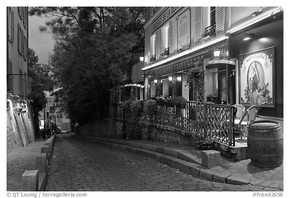 Cobblestone street and restaurant at dusk, Montmartre. Paris, France (black and white)
