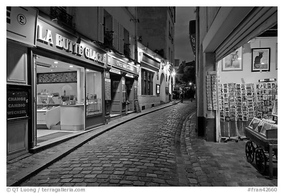 Narrow cobblestone street and businesses at night, Montmartre. Paris, France (black and white)