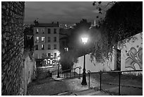 Hillside stairs of butte Montmartre and street lights at sunset. Paris, France (black and white)