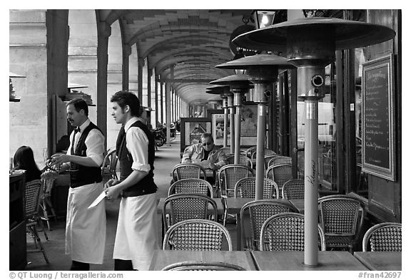 Waiters and cafe in place Victor Hugo arcades. Paris, France (black and white)