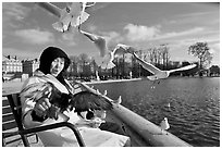 Elderly woman and seagulls, Tuileries garden. Paris, France (black and white)