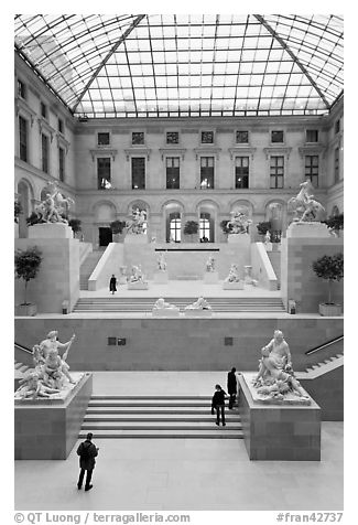 Tourists and exhibit inside Louvre museum. Paris, France (black and white)