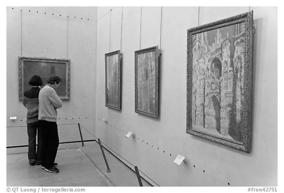 Tourists looking at Monet's Rouen Cathedral, Orsay Museum. Paris, France (black and white)