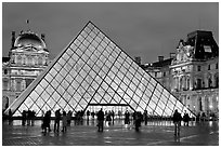 People standing in front of Louvre Pyramid by night. Paris, France (black and white)
