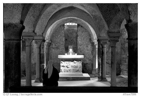 Crypte of the Romanesque church of Vezelay with Nun in prayer. Burgundy, France (black and white)