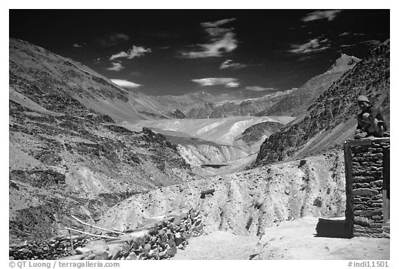 Woman sitting on roof of house in front of mountain landscape, Zanskar, Jammu and Kashmir. India (black and white)
