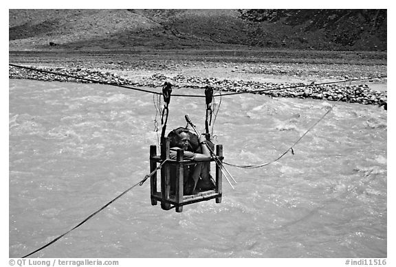 Trekker crossing a river by cable, Zanskar, Jammu and Kashmir. India (black and white)