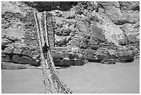 Man crossing a river by rope bridge, Zanskar, Jammu and Kashmir. India ( black and white)