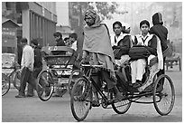 Cycle-rickshaw carrying uniformed schoolgirls. New Delhi, India ( black and white)