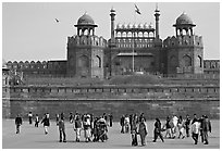 Tourists walking on esplanade in front of the Lahore Gate. New Delhi, India (black and white)