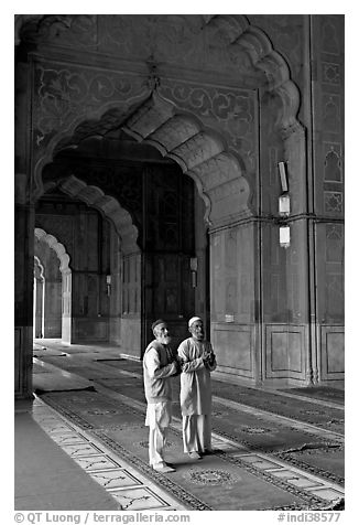 Two muslem men in Jama Masjid mosque prayer hall. New Delhi, India (black and white)