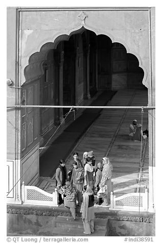 Women standing beneath arched entrance of prayer hall, Jama Masjid. New Delhi, India (black and white)