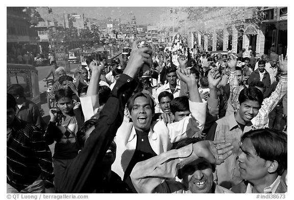 Young men celebrating and spraying wedding party in the street. Jodhpur, Rajasthan, India (black and white)