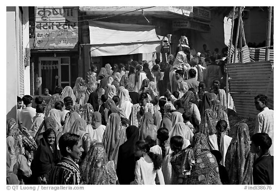 Street with women in colorful sari following wedding procession. Jodhpur, Rajasthan, India (black and white)