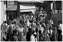 Street with women in colorful sari following wedding procession. Jodhpur, Rajasthan, India ( black and white)
