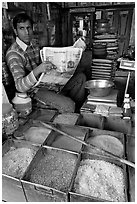Man with newspaper selling grains, Sardar Market. Jodhpur, Rajasthan, India (black and white)