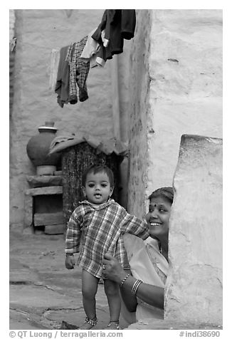Baby girl and woman in blue alley. Jodhpur, Rajasthan, India (black and white)
