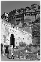 Couple walking below gate and high walls, Mehrangarh Fort. Jodhpur, Rajasthan, India (black and white)