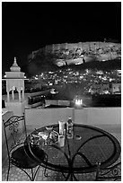 Rooftop restaurant table with food served and view of Mehrangarh Fort by night. Jodhpur, Rajasthan, India (black and white)