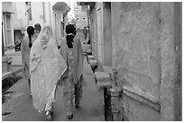 Women walking in narrow alley with blue walls. Jodhpur, Rajasthan, India (black and white)