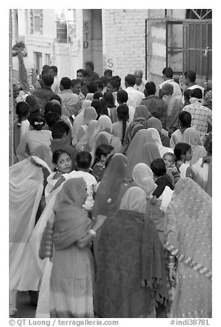Narrow street filled by wedding procession. Jodhpur, Rajasthan, India (black and white)