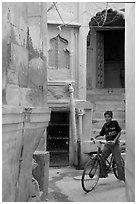 Boy riding a bicycle in a narrow old town street. Jodhpur, Rajasthan, India (black and white)