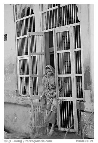 Woman stepping out of door. Jodhpur, Rajasthan, India (black and white)