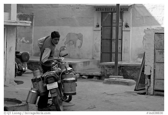 Man with milk delivery motorbike. Jodhpur, Rajasthan, India (black and white)
