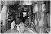Men in shop selling colorful fabrics, Sardar market. Jodhpur, Rajasthan, India (black and white)