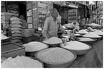 Man in front of grain and spice store, Sardar market. Jodhpur, Rajasthan, India (black and white)