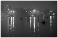 Rowboats and reflected lights on the Ganges River at dusk. Varanasi, Uttar Pradesh, India (black and white)