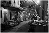 Flower vendor in  narrow old city alley at night. Varanasi, Uttar Pradesh, India ( black and white)