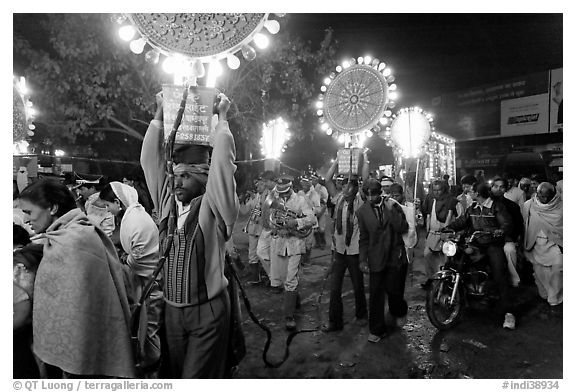 Men carrying bright electric signs during wedding procession. Varanasi, Uttar Pradesh, India (black and white)