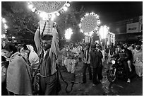 Men carrying bright electric signs during wedding procession. Varanasi, Uttar Pradesh, India ( black and white)
