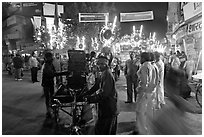 Men pulling generator on bicycle to power lights during wedding procession. Varanasi, Uttar Pradesh, India (black and white)